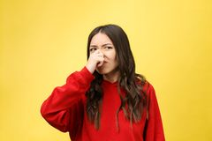 Smell bad. Young lady makes disgusts the smell isolate on yellow background. Smell bad. Young lady makes disgusts the smell isolate on yellow background stock images