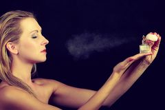 Beautiful woman with holding and applying perfume stock photo