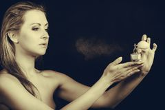 Beautiful woman with holding and applying perfume royalty free stock photo