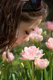 Smell the Flower. A young girl smelling a pink flower Stock Image