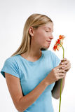 Smell flowers. Beautiful young woman smelling a red flower, isolated on white Royalty Free Stock Images