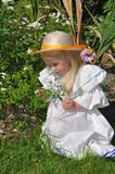 Smell the flowers. Small girl smelling flowers in the garden Stock Image