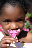 Smell the Flowers. A young girl smells the pretty pink flower on a beautiful spring day Royalty Free Stock Photo