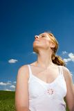 Smell the fresh air. Woman with closed eyes and airy wear. Head towards the sun. Recreation, smelling the fresh air. Blue sky with white clouds as background Royalty Free Stock Images
