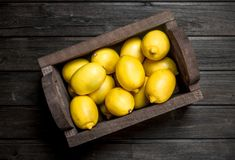 The smell of fresh lemons in wooden box. On black wooden background stock photo