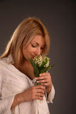 The smell of lily of the valley. Beautiful girl sniffing flowers, lily of the valley Stock Photos