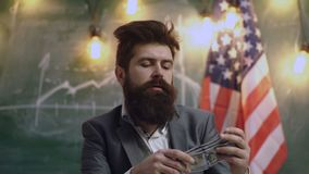 Smell of money. Easy cash loans. Man formal suit hold pile of dollar banknotes on background of USA flag. Businessman. Got cash money. Richness and wellbeing stock footage