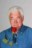 Smell of the rose. Handsome mature man holding a red rose royalty free stock photo