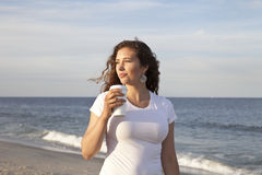 Smell the Roses. Woman enjoying cup of coffee at the beach Royalty Free Stock Photo