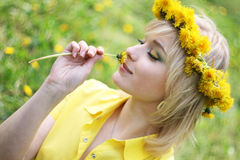 Smell of spring. The young pretty girl smells a dandelion Stock Image