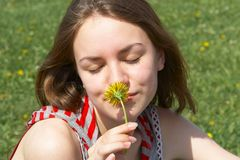 Smell of summer. Portrait of the nice young girl with a yellow flower Stock Photo