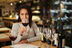 Smell of wine. Modern sommelier holding glass of red wine and evaluating its smell while comparing it with other sorts Royalty Free Stock Photos