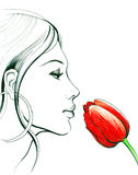 Smelling a flower. Beautiful woman is smelling a red flower Stock Photo