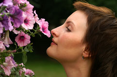 Smelling flowers. Beautiful young woman smelling flowers Stock Photos