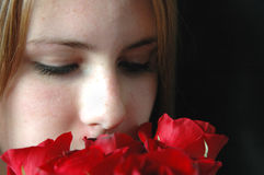 Smelling the roses. A close up of a girl smelling red roses on a black background Royalty Free Stock Photography