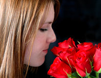 Smelling the roses. A profile of a pretty girl smelling red roses on a black background Stock Photography