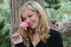Smelling the roses. Blonde smelling a rose royalty free stock images