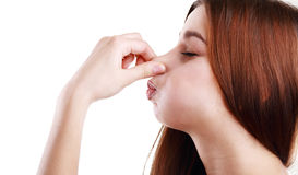 Smelling something stinking. Young Woman Holding her Nose smelling something stinking royalty free stock photo