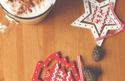Smells like Christmas. Latte in a glass cup with cinnamon on a wooden table and some wood Christmas decorations for Christmas tree Stock Images