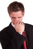 Smells terrible. A business man smells something bad. All in front of white background stock photo