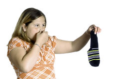 Smelly Sock. A young girl plugging her nose because of the smell of a stinky sock, isolated against a white background Stock Image