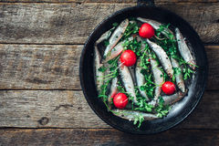 Smelt fish in the pan. Smelt fishes in old pan on wooden background with blank space Royalty Free Stock Photography
