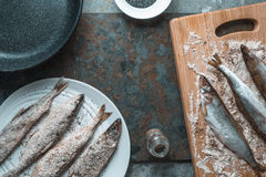 Smelt on a plate and on a cutting board, frying pan Royalty Free Stock Photos
