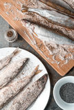 Smelt on a plate and on a cutting board. Vertical Royalty Free Stock Photography