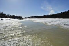 Smeltend overzees ijs in de lentezon met bos en blauwe hemel Stock Foto