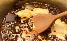 Smeltende boter en chocolade samen in een pan stock foto