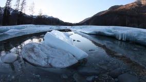 Smeltende gletsjer op de rivier in de lente in de bergen stock footage