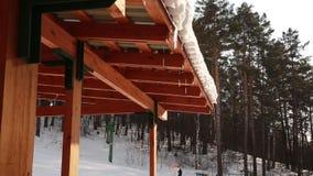 Smeltende Ijskegels die van een dak druipen De lente daalt, smelten de ijskegels zon en sneeuw de lente in de skitoevlucht stock videobeelden