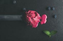 Smeltende lepel van bosbessenroomijs over de zwarte achtergrond van de leisteen Royalty-vrije Stock Fotografie
