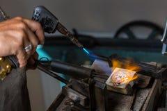 Smeltende Zilveren Korrels in smeltkroes met soldeerlamp stock afbeeldingen