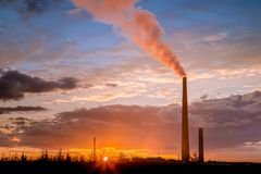 Smelter stack of a nickel plant. View of a smelter stack of a nickel plant showing the emission on the air with sunset sky as as background Royalty Free Stock Photo