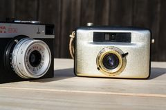 Smena 8M and Penti I old vintage golden cameras on wooden background stock photos