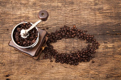 Smerigliatrice d'annata del chicco di caffè accanto ai chicchi di caffè di forma del cerchio Immagine Stock