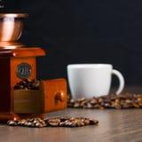 Smerigliatrice del caffè, chicchi di caffè e tazza di caffè antichi. Fotografie Stock