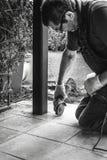 Smerigliatrice del lavoratore dell'uomo che taglia le mattonelle sulla veranda immagini stock