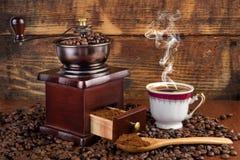 Smerigliatrice del mulino di caffè e tazza di caffè con fumo e cucchiaio di legno su retro fondo fotografie stock libere da diritti