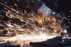 Smerigliatrice di angolo Un uomo che lavora con lo strumento elettrico su una parte di metallo, scintille della smerigliatrice ch Immagini Stock