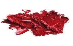 Smetad röd läppstift på vit bakgrund Arkivbild