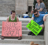 Smetta di bombardare Gaza, cada i segni del blocco a raduno Fotografie Stock Libere da Diritti