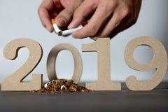 Smetta di fumare 2019, fumando il giorno 2019 di cessazione su un fondo nero e sulle mani che stanno distruggendo le sigarette fotografie stock