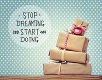 Smetta di sognare l'inizio che fa il messaggio con i contenitori di regalo immagini stock