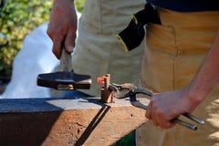 Smid aan het werk, met een hamer door een heet metaal op het aambeeld stock afbeelding