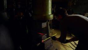 Smid die candent ijzerbaar houden en het smeden die pneumatische hamer gebruiken stock footage