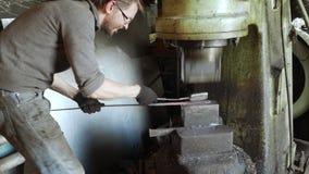 Smid die candent ijzerbaar houden en het smeden die pneumatische hamer gebruiken stock videobeelden