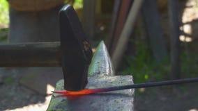 Smid die het gesmolten metaal op het aambeeld in smidse smeden stock videobeelden
