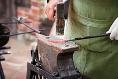 Smid met een hamer in zijn handen het werken stock foto